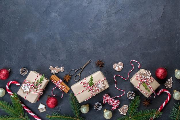Cornice di natale scuro con regali di natale e zucchero filato, decorazioni, pigne, rami di abete. lay piatto
