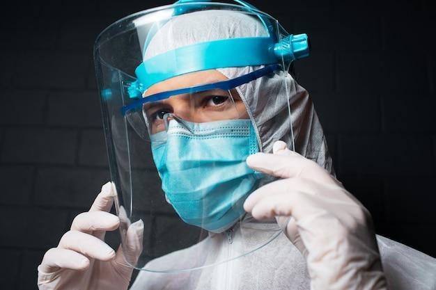 Ritratto scuro del primo piano di un giovane medico che indossa la tuta dpi contro il coronavirus e il covid-19. sullo sfondo di un muro di mattoni neri.