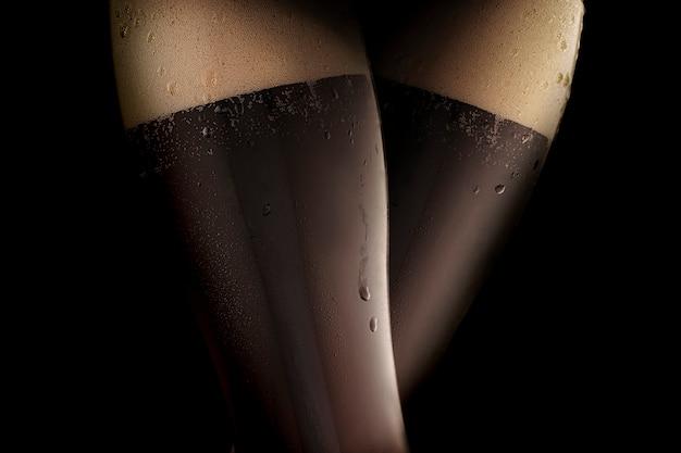 Birra fredda scura in due bicchieri al vapore, simili a gambe femminili sexy in calze nere. sfondo nero.