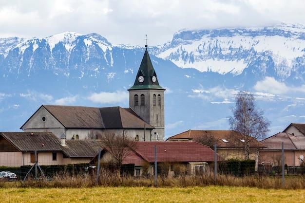Siluetta scura di contrasto del tetto della chiesa con la torre contro le montagne magnifiche delle alpi, germania. vita tranquilla su cime fantastiche con neve splendente sotto un cielo blu brillante con nuvole bianche gonfie.