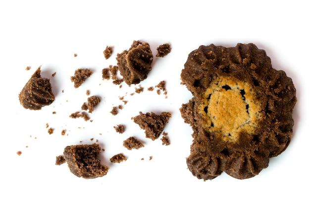 Biscotti scuri sotto forma di un fiore rotto su bianco. vista dall'alto.