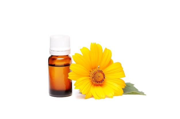 Bottiglia cosmetica scura di olio aromatico per erboristeria con fiore di calendula isolato su bianco