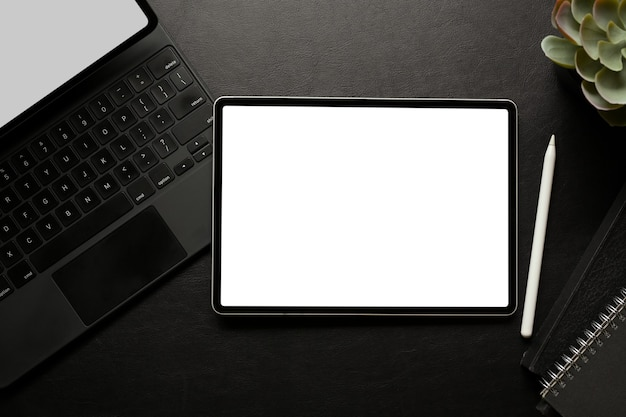 L'area di lavoro creativa scura con tavoletta digitale include la tastiera dello schermo del tracciato di ritaglio e la vista dall'alto della cancelleria