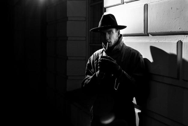 Sagoma scura drammatica di un uomo con un cappello fumare una sigaretta per strada di notte in stile noir