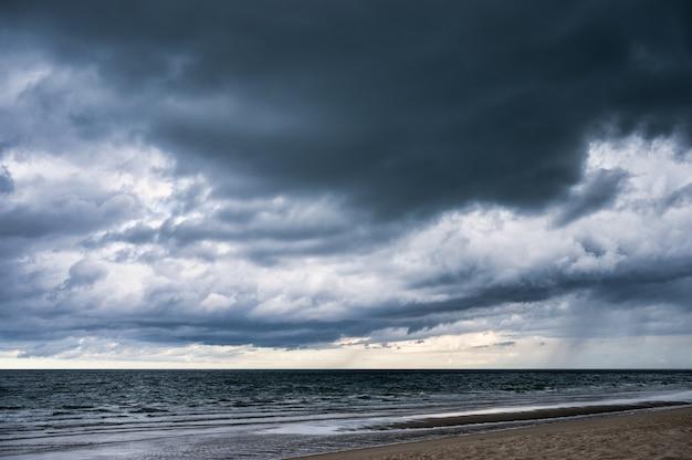 Cielo drammatico scuro e nuvole tempestose sul mare tropicale