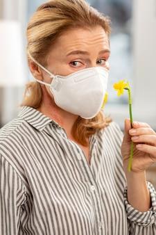 Donna matura dagli occhi scuri che indossa una maschera sul viso con allergia ai fiori