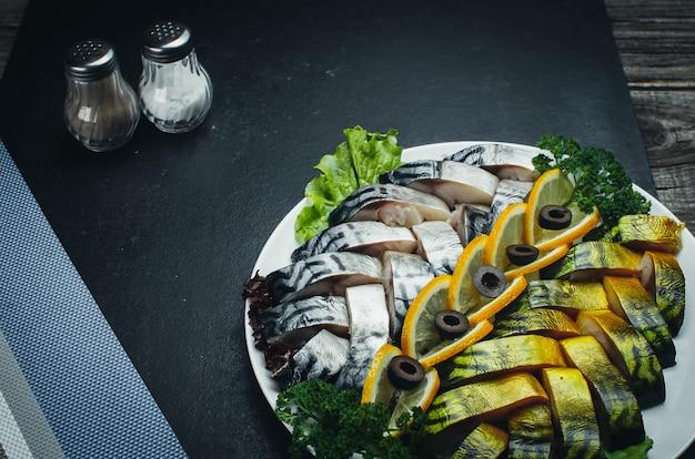 Su tessuti scuri, sul piatto c'è un bel pesce, aringa e salmone decorato con verde
