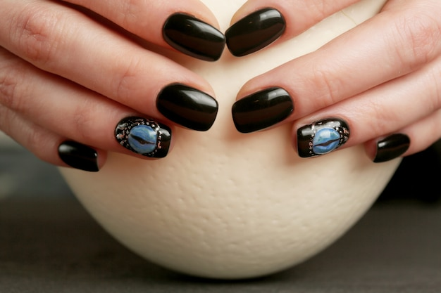Nail art dark fantasy sul primo piano di mani ben curate