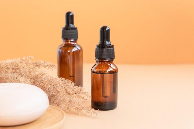 Bottiglie di vetro scuro con oli essenziali e saponetta per il viso su fondo beige. concet per la cura della pelle con copy soace. cosmetici naturali.