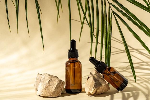 Flaconi per la cosmetica in vetro scuro con contagocce su superficie beige con pietre e foglie tropicali