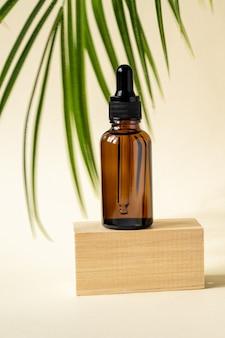 Flacone contagocce in vetro scuro con olio cosmetico, essenziale o siero su supporto in legno con foglia di palma