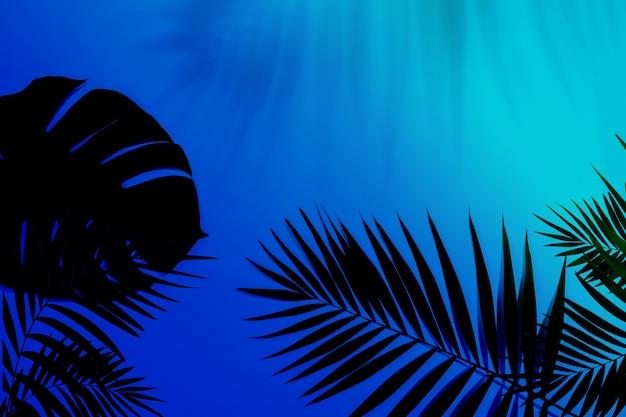 Foglie di palma tropicale verde scuro isolate su sfondo sfumato blu viola. design per biglietti d'invito, volantini. modelli di design astratti per poster, copertine, sfondi con copyspace per il testo.