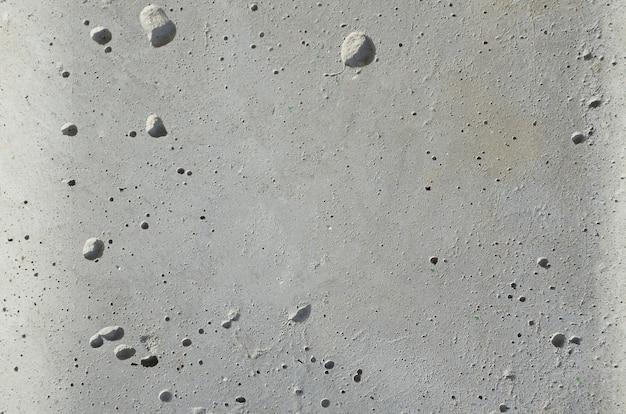 Struttura di cemento grigio scuro, muro di pietra di cemento grezzo, ghiaia di superficie del vecchio e sporco muro di edificio all'aperto.