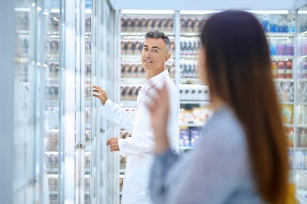 Cliente femminile caucasica dai capelli scuri che chiama un farmacista maschio sorridente bello in una veste bianca