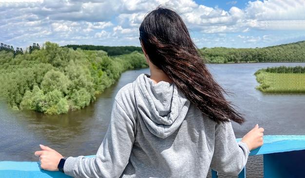 Una ragazza caucasica dai capelli scuri sta con la schiena in una giacca grigio chiaro e guarda verso il fiume e la foresta nella città di chernigiv in ucraina.
