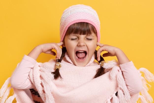 La ragazza dai capelli scuri copre le orecchie con il dito