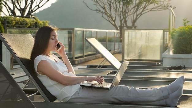 Ragazza dai capelli scuri parla su smartphone e messaggi su laptop che riposa su una sedia pieghevole in hotel contro la collina al mattino