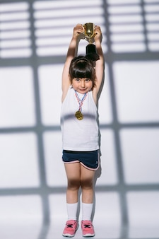 Ragazza dai capelli scuri con medaglie del campionato sportivo, alzando la coppa del trofeo con le mani, sopra le ombre di una finestra con l'otturatore sopra di lei. sport e concetto di vittoria