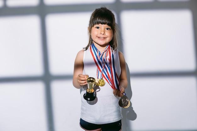 Ragazza dai capelli scuri con medaglie del campionato sportivo e coppa del trofeo, in piedi all'ombra di una finestra con una tenda sopra di lei. sport e concetto di vittoria