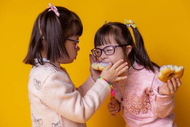 Signora dai capelli scuri che si alimenta. curiose gemelline di bell'aspetto mangiano insieme mentre le mettono in bocca una ciambella glassata