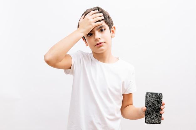 Bambino dai capelli scuri che tiene la bocca del coperchio dello smartphone rotto con la mano scioccata dalla vergogna per l'errore, espressione di paura, paura in silenzio, concetto segreto