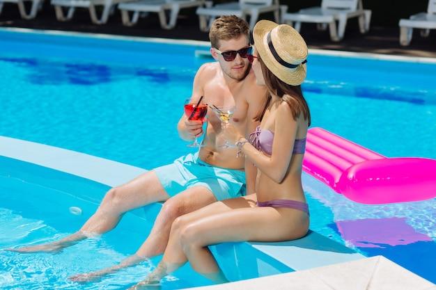 Uomo dai capelli scuri che indossa occhiali da sole scuri a parlare con una donna attraente seduta in piscina