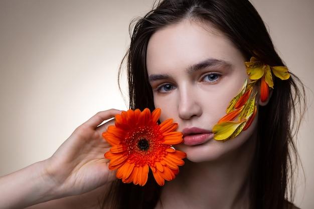 Modello dai capelli scuri in piedi vicino a un muro chiaro con in mano un bel fiore arancione