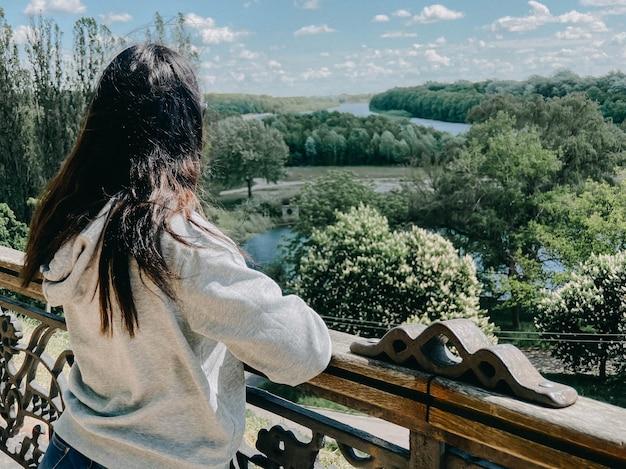 Una ragazza aucasica dai capelli scuri sta con la schiena in una giacca grigio chiaro e guarda verso il fiume e la foresta nella città di chernigov in ucraina.