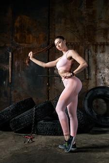 Coach donna dai capelli scuri con top sportivo rosa e leggings da ginnastica