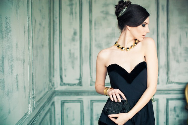 Donna dai capelli scuri in elegante abito nero con borsa della frizione in piedi all'interno della stanza
