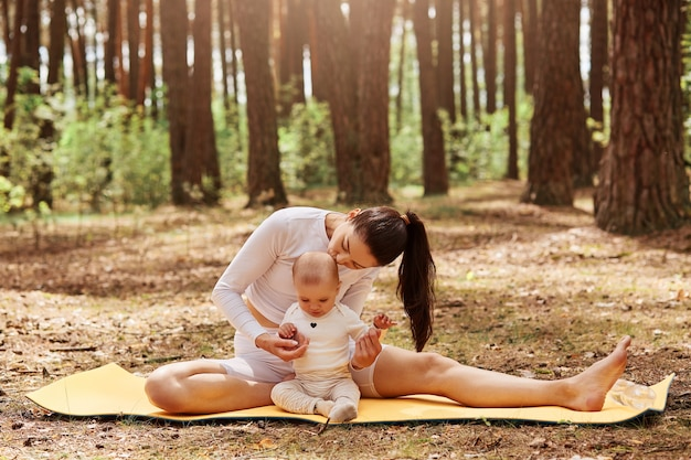 Donna dai capelli scuri con coda di cavallo seduta su karemat con la sua piccola figlia, madre che bacia il suo bambino