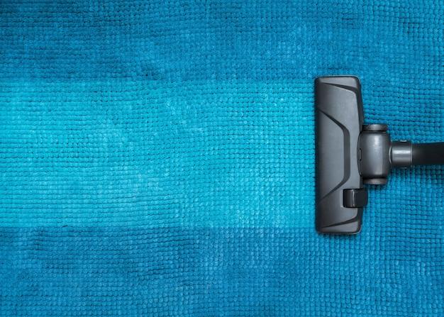 Testa scura di un moderno aspirapolvere utilizzato durante l'aspirazione di un tappeto.