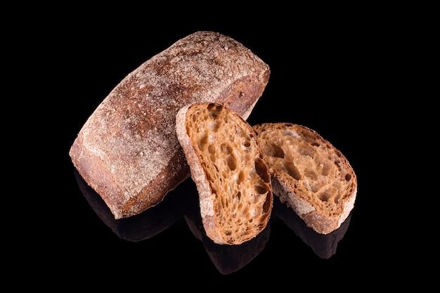 Pane a fette ciabatta italiano scuro. pane fatto in casa appena sfornato isolato sul nero. mangiare sano e panetteria tradizionale, concetto di pane da forno.