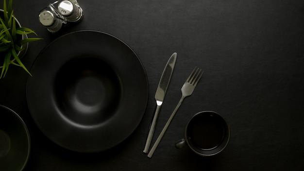 Tavolo da pranzo di lusso scuro con piatto in ceramica nera, argenteria, bottiglie di condimento, spazio di copia e decorazione