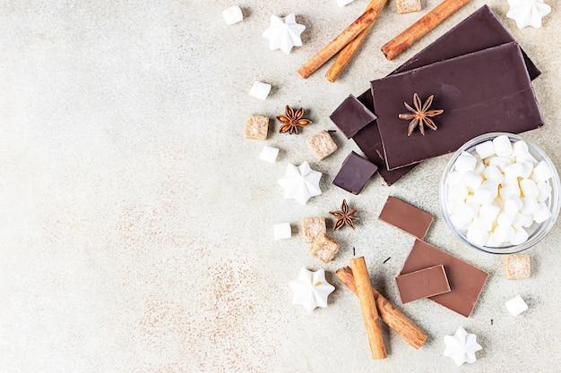 Pezzi di barretta di cioccolato fondente e al latte, spezie, zucchero di canna, meringa e marshmallow. cibo dolce.