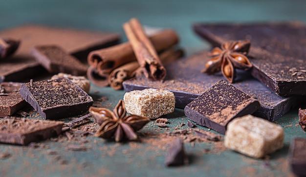 Pezzi di cioccolato fondente e al latte, cacao in polvere, cannella, anice stellato e zucchero di canna sulla superficie della pietra