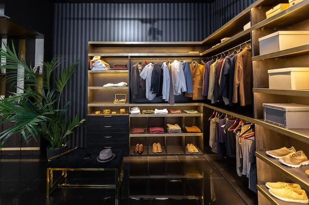 Interno di appartamento maschile elegante moderno scuro con illuminazione, pareti decorative, camino, spogliatoio e finestra enorme
