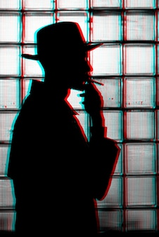 Sagoma mistica scura di un uomo con un cappello che fuma una sigaretta. bianco e nero con effetto di realtà virtuale glitch 3d