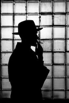 Sagoma mistica scura di un uomo con un cappello che fuma una sigaretta di notte in stile retrò noir
