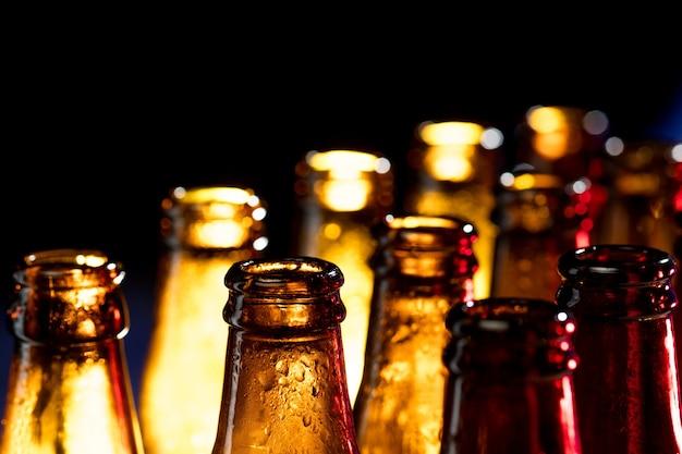 Buio. bottiglie di birra colorate al neon, primo piano isolato su sfondo luminoso per studio. concetto di birra, bevande, intrattenimento e alcol. copyspace per la pubblicità di bar, ristoranti, birrerie o negozi.