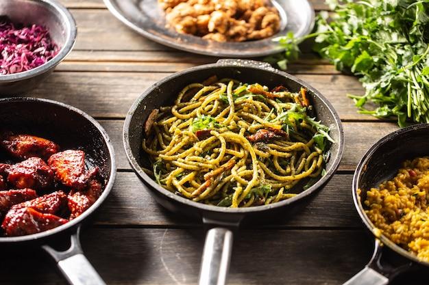 Pentole scure con vari cibi come spaghetti al pesto, risotti e alette di pollo glassate.