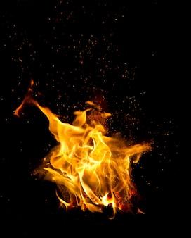 Foto scura di un fuoco con fiamme arancioni che sputano scintille intorno.