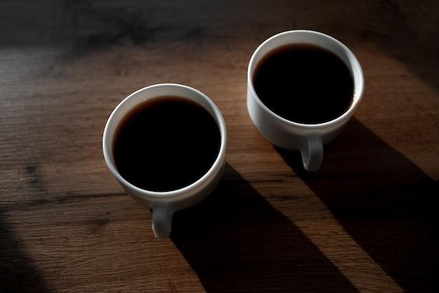 Foto scura di due tazze di caffè in ceramica su un tavolo di legno. primo piano vista dall'alto.