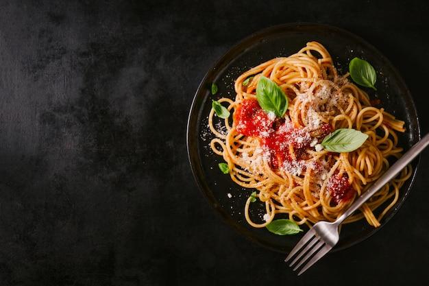 Piatto scuro con spaghetti italiani su oscurità