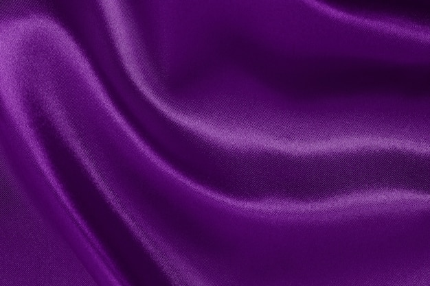 Sfondo trama tessuto viola scuro, motivo sgualcito di seta o lino.