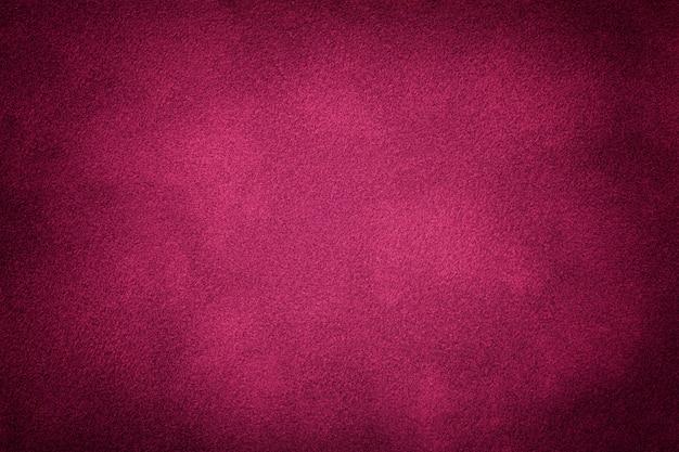 Primo piano del tessuto scamosciato opaco viola scuro. trama di velluto.