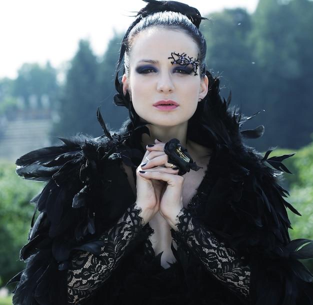 Dark queen nel parco in abito nero fantasia