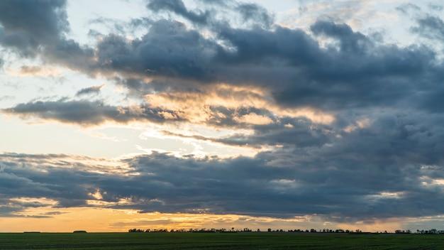 Nuvole scure di pioggia sopra il campo al tramonto.