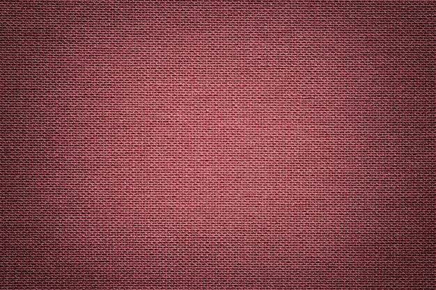 Sfondo rosso scuro da un materiale tessile. tessuto con trama naturale.