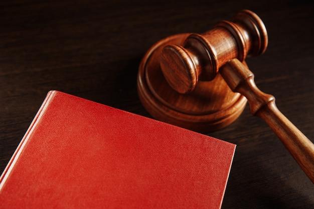 Libro rosso scuro e martelletto di legno su di esso.